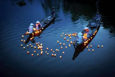 Hue City, central Vietnam: girls in traditional dresses float candles in the river in prayer for loved ones who have passed on.