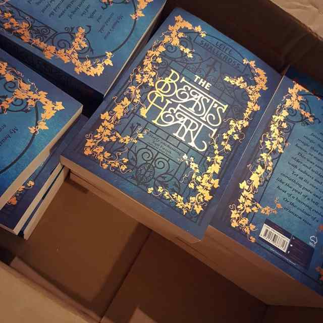 A box full of paperback books, titled The Beast's Heart. The cover is decorated with shiny coppery ivy.