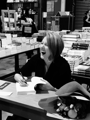A woman sitting at a table. She is holding a pen and has paused in the act of writing something in the book open in front of her. She is laughing.