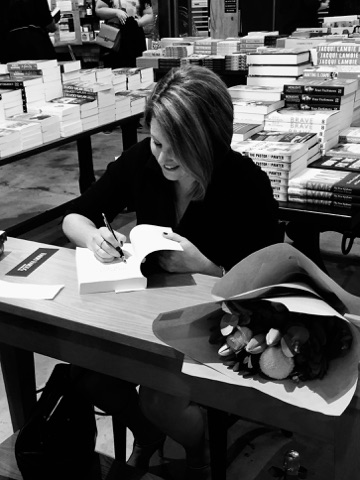 A woman sitting at a small desk with a book open in front of her. She is writing on the first page of the book. She is looking down at the book and smiling.